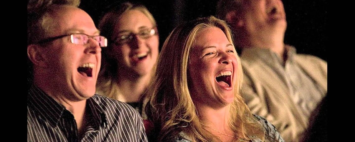 audience members laughing at comedy performer